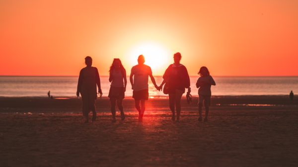 people walking together toward a sunset at the beach (orange glow background)